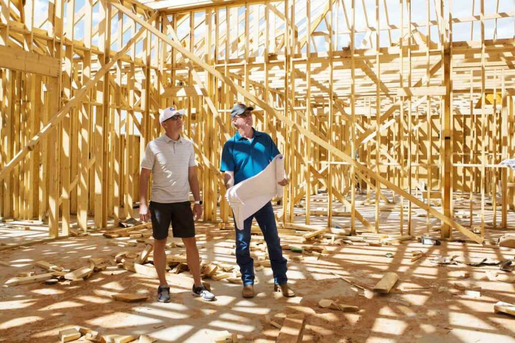 Owners Mike & Lucas reviewing a house framing job with plans